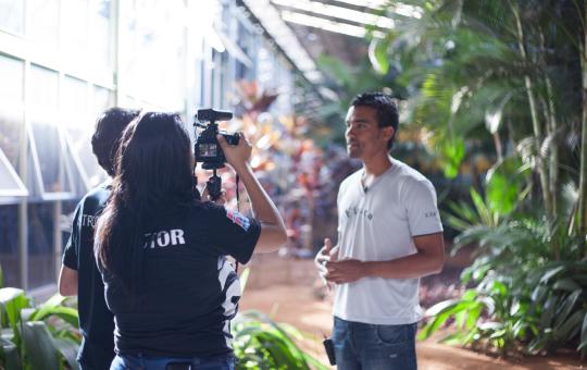 Dois alunos da produtora com equipamentos filmando o depoimento de um homem de pé.