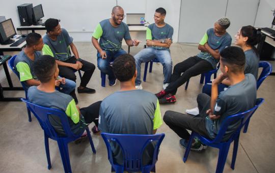 Jovens sentados em cadeiras num círculo, conversando e rindo